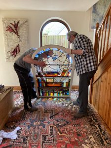 Stained Glass window installation with two people