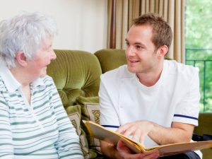 Young male carer reading to elderly woman