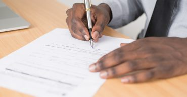 Man holding a pen completing an application form