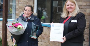 Two women at award presentation with flowers and certificate