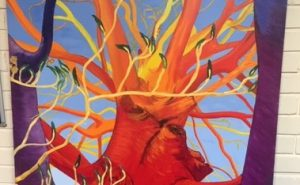 Red, yellow and purple abstract painting of a tree