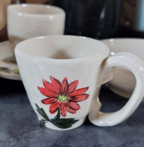 White teacup with red flower design