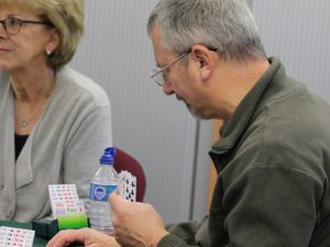 Man and woman playing card game bridge