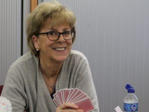 Woman in grey cardigan holding playing cards
