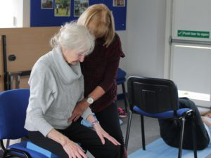 older woman sitting in a chair with tutor practising Alexander Technique