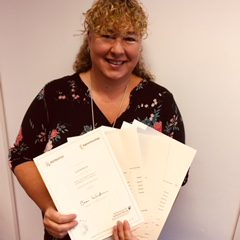 Lady with blond curly hair holding certificates
