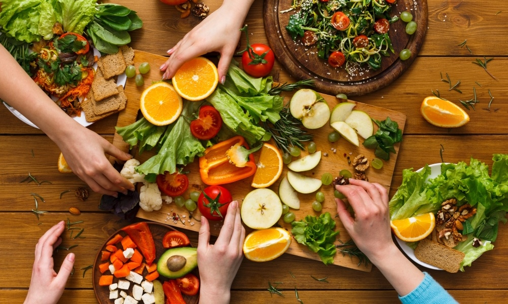 Platter of fruit and vegetables with hands selecting them