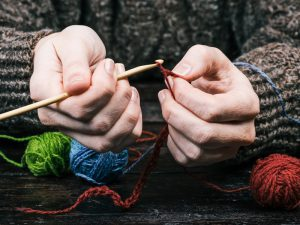 hands using wool to crochet with hook