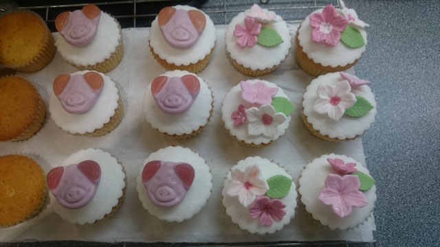 Cupcakes decorated with pig sweets and flowers
