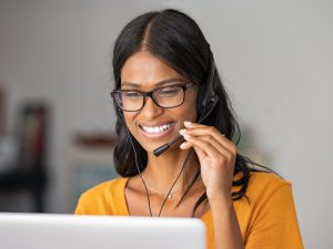 Smiling young woman at home with headset doing video call