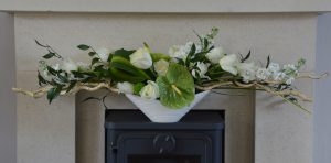 Floral arrangement with white flowers and green foliage