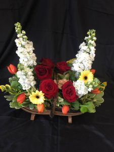 Flower arrangement with red roses, yellow gerberas and orange tulips
