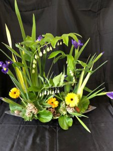 Floral design with green foliage and yellow gerbera flowers