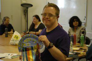 Man holding up a piece of craft made in an ALDD class