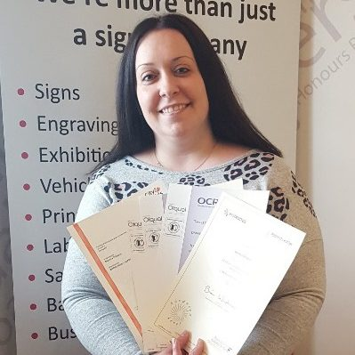 lady with long dark hair holding certificates