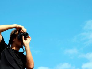 Person holding Black digital camera with blue sky behind