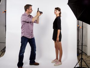 Man taking photograph of girl in studio with umbrella