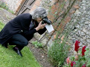 Woman kneeling on grass taking photograph of flowers