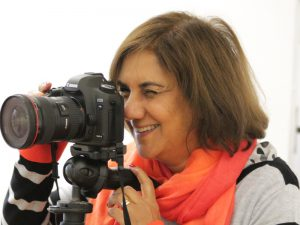 Woman looking through viewfinder on digital camera on tripod
