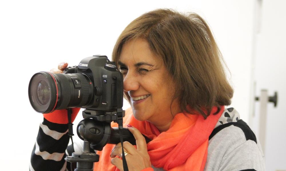Woman looking through viewfinder on digital camera on tripod