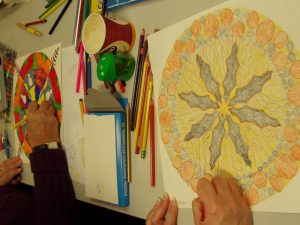 Two people drawing mandalas