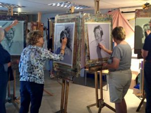 Four people drawing portraits on easels