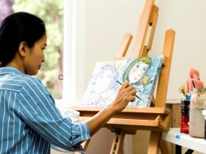Woman in blue striped shirt painting a picture on an easel