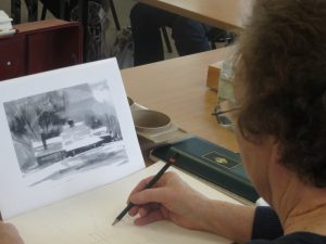 Woman drawing a picture from a black and white picture