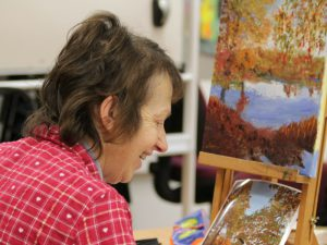 Woman in pink shirt painting on an easel
