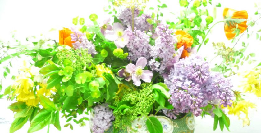 Flower arrangement in vase with lilacs and green foliage