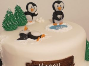 White christmas cake with model penguins