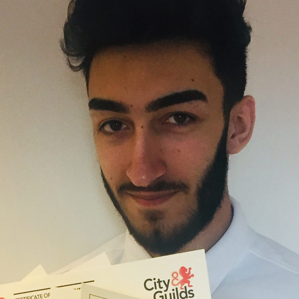 Young man with beard holding certificates