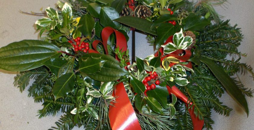 Christmas wreath with green foliage and red berries and ribbon