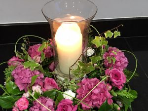 Pink and green flower arrangement with glass vase and candle in the middle