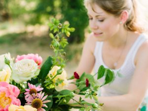 Woman in white vest arranging pink and white flowers