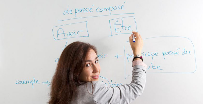 Woman writing on French verbs on whiteboard