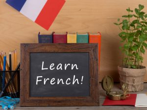 Blackboard with Learn French written on it, pot of pencil and French flag