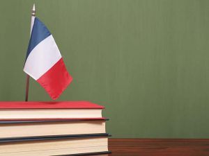 Books and flag of France on desk in front of green chalkboard