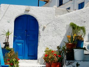Blue door in white house with flowerpots in front