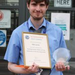 Young man with award and certificate