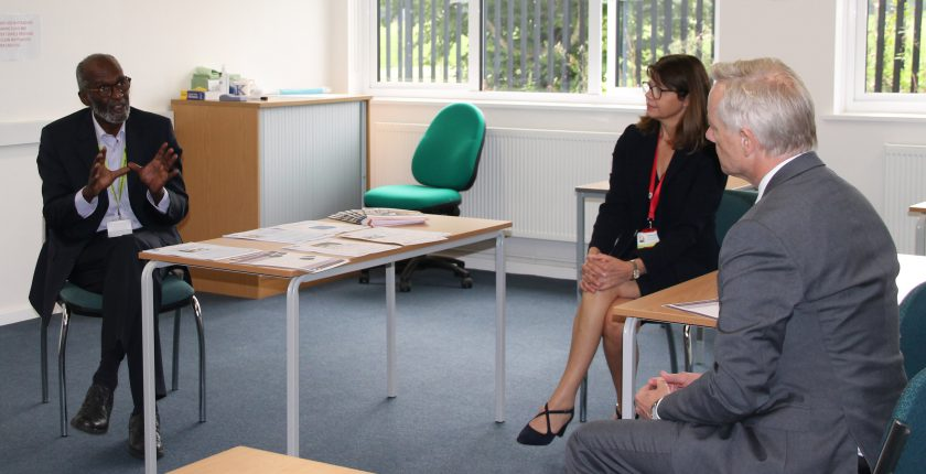 Two men and one woman talking in a classroom