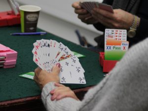 Woman in grey sweater holding cards for bridge game