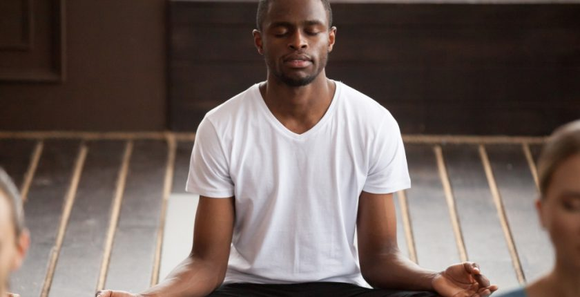 Man sitting in yoga pose with eyes closed