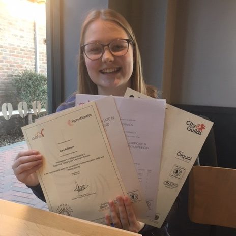 Girl with glasses and blond hair holding certificates