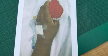 Hospital patient holding a knitted heart