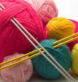 Balls of coloured wool with knitting needles