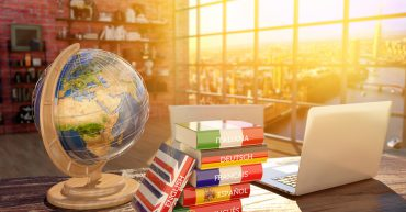 A globe, a pile of language books and a laptop on a desk