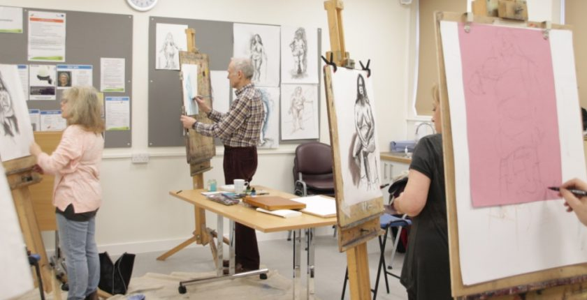 4 people in a classroom with easels drawing a live model