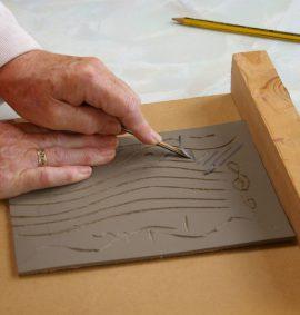 Hands cutting a lino print template