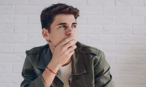 Young man thinking with hand over his face